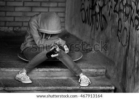 Teen girl in hood holding a beer bottle and sitting on the stairs in the alley