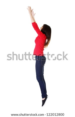 Teen girl jumping in air trying to catch something. Isolate don white. - stock photo
