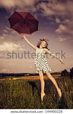 teen girl jumping with an umbrella in front of rural landscape - stock photo