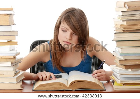 Teen girl learning at the desk with lot of books, isolated on white - stock photo