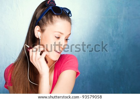 teen girl listen music on earphones, studio shot