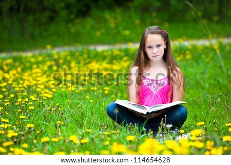 Teen-girl (looking at the camera) reads a book in the meadow - stock photo