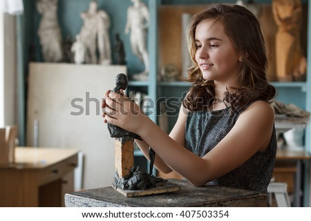 Teen Girl molds from clay sculpture in the artist's studio. - stock photo