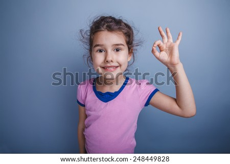 Teen girl of European appearance, brunette showing thumbs up sign okay on a gray background - stock photo