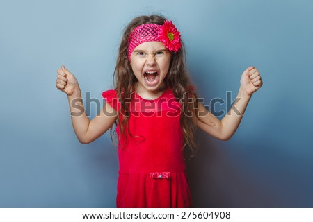 teen girl of European appearance five years angry opened her mouth on a gray background - stock photo