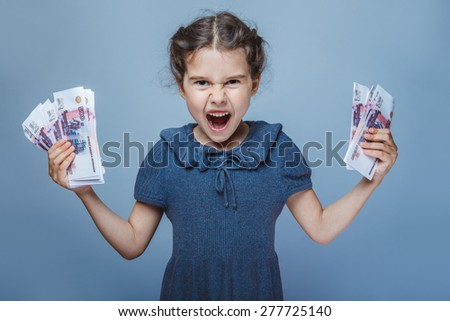 teen girl of European appearance holds five denominations of money in the hands of angry shouts opened her mouth on a gray background