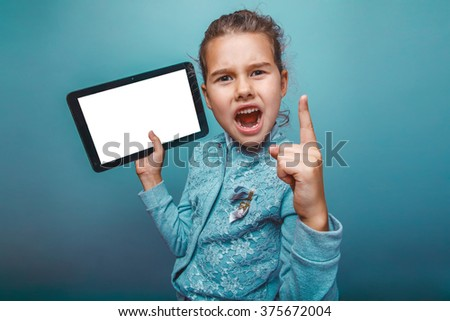 teen girl of European appearance seven years  shows a finger up the angry idea of holding a tablet in the hands on a gray background - stock photo