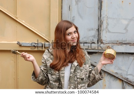 Teen girl painting old gate.Ukraine