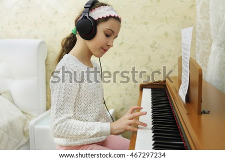 teen girl playing on synthesizer melody, put headphones on her head