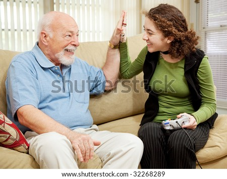 Teen girl playing video games, getting a high five from her grandfather.