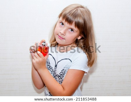 Teen girl poses with red parfume bottle in her hands - stock photo
