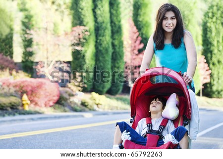 Teen girl pushing her little disabled  brother in stroller outdoors