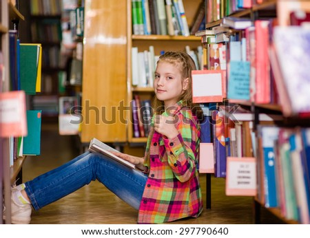 Teen girl reading a book on the floor in the library and showing thumbs up - stock photo