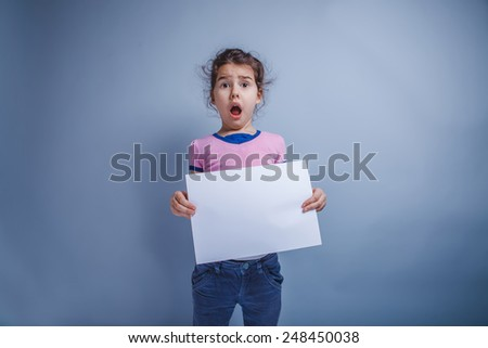 Teen girl seven years of European appearance, holding a sheet of white paper opened her mouth on a gray background, surprise - stock photo