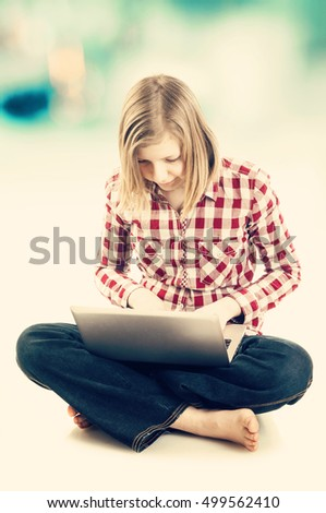 Teen girl sitting and using laptop, toned image