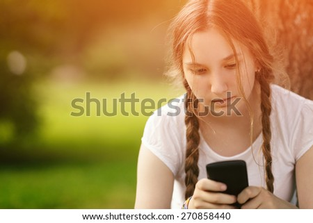 teen girl sitting near tree with mobile phone outdoors - stock photo