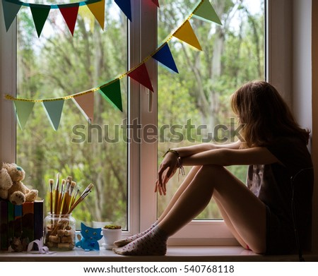teen girl sitting on a windowsill in the children's room