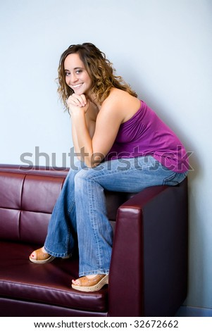 teen girl sitting on couch - stock photo