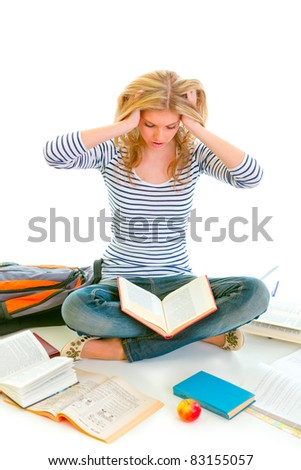 Teen girl sitting on floor among schoolbooks and studying hard isolated on white - stock photo