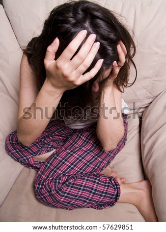 Teen girl sitting on the chair holding head and crying
