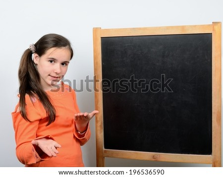 Teen girl standing at the blackboard at school - stock photo