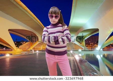 Teen girl standing under bridge at night - stock photo
