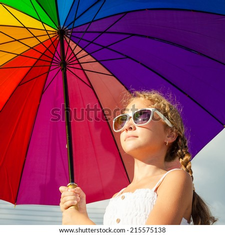 teen girl standing with umbrella on the blue sky background at the day time - stock photo