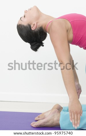 Teen girl stretching her back in yoga pose - stock photo