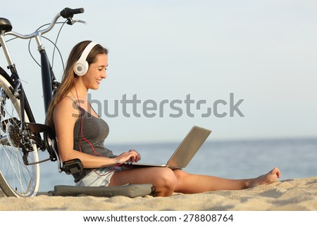 Teen girl studying with a laptop on the beach leaning on a bicycle - stock photo