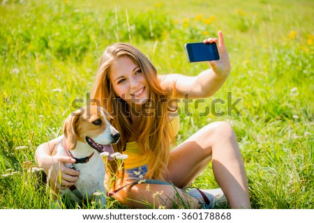 Teen girl taking photo of herself and her dog with mobile phone camera - stock photo