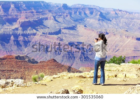 Teen girl taking pictures at the Grand Canyon with cell phone. - stock photo