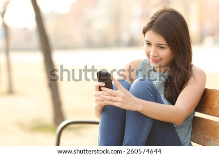 Teen girl using a smart phone and texting sitting in a bench of an urban park - stock photo