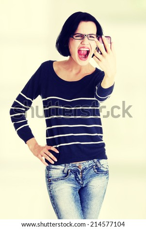 Teen girl using cell phone- yelling angry, isolated on white - stock photo