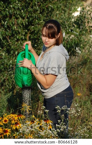 Teen girl watering garden.Near Kiev,Ukraine