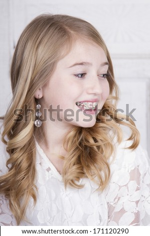 Teen girl wearing braces wearing white looking off to side