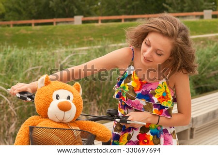 teen girl with a bicycle and a teddy bear