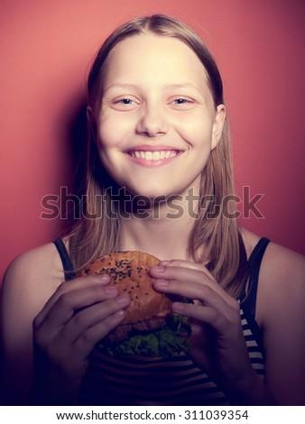 Teen girl with a delicious burger - stock photo