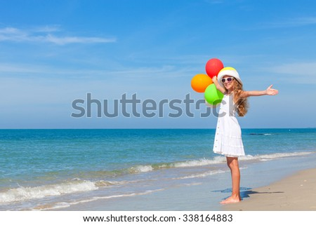 Teen girl with balloons standing on the beach at the day time