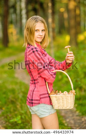Teen girl with basket of mushrooms showing honey agaric.