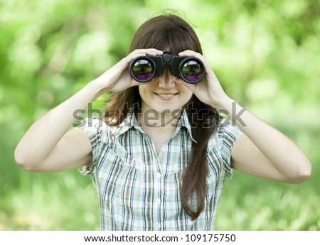 Teen girl with binocular at green grass - stock photo