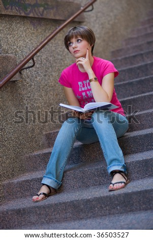 teen girl with book on the stairs - stock photo