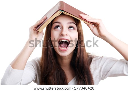 Teen girl with book over her head, isolated on white yelling - stock photo