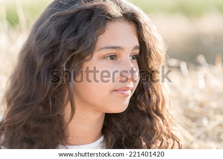Teen girl with curly dark hair on a nature