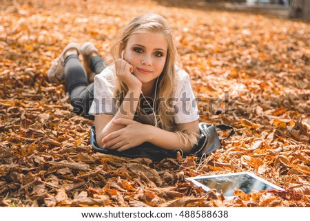 Teen girl with digital tablet lying on leaves
