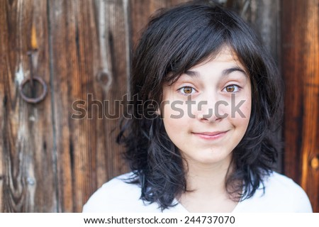 Teen girl with expressive eyes closeup portrait against a wooden wall. - stock photo