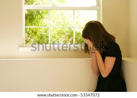 Teen girl with her head in her hands - stock photo