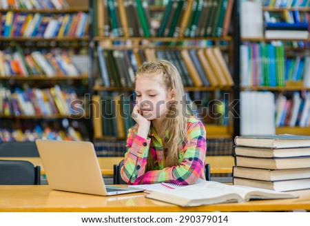 Teen girl with laptop in library