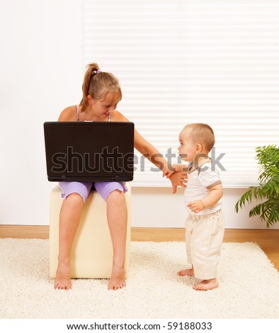 Teen girl with laptop, pushing away her little brother to let herself alone