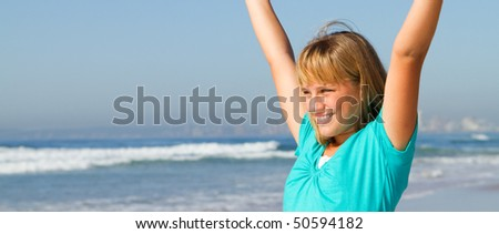 teen girl with open arms on beach - stock photo