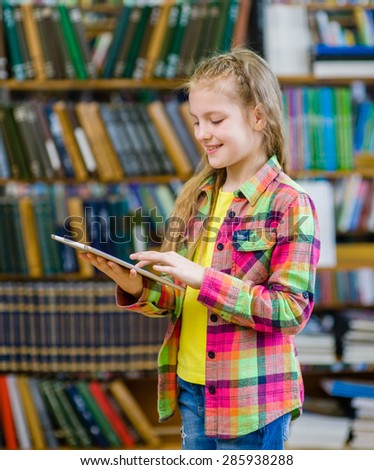 Teen  girl with tablet computer in a library - stock photo